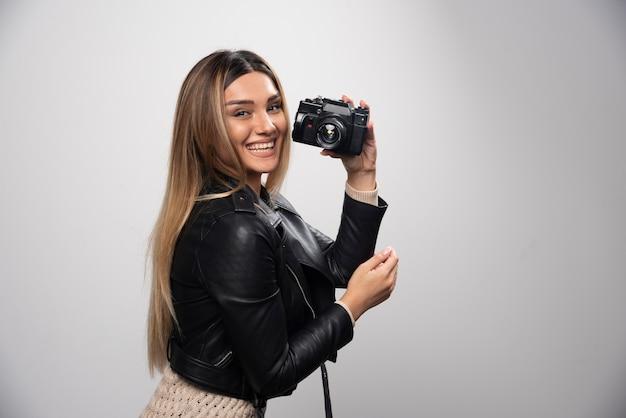 Chica con chaqueta de cuero tomando sus fotos en posiciones elegantes y positivas.