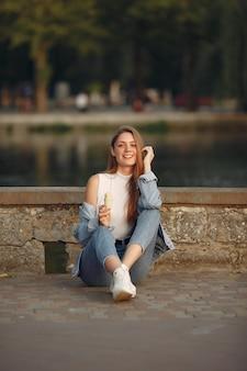 Chica en una chaqueta de jeans azul en una ciudad de verano