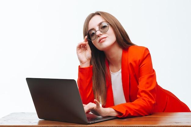 Chica en una chaqueta roja trabajando en la computadora sobre un fondo blanco.