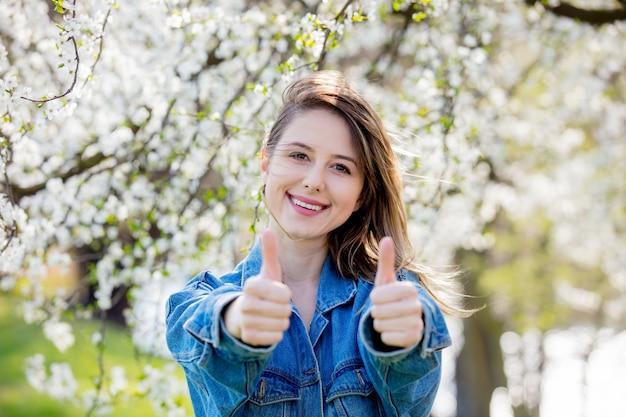 La chica con una chaqueta vaquera se encuentra cerca de un árbol en flor y muestra el signo de la mano ok