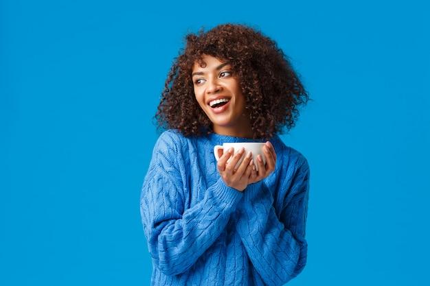 Chica con chat con novia mientras bebe café. alegre y linda mujer encantadora afroamericana con corte de pelo afro, en suéter, con la cabeza inclinada mirando a la izquierda y sosteniendo una taza de té delicioso