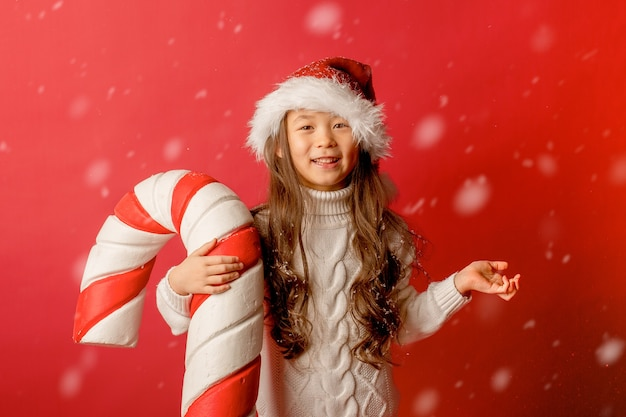 Chica chica asiática con gorro de papá noel en un toque el fondo con un caramelo grande para coger la nieve