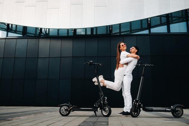 Una chica y un chico caminan en patinetes eléctricos por la ciudad, una pareja enamorada en patinetes.