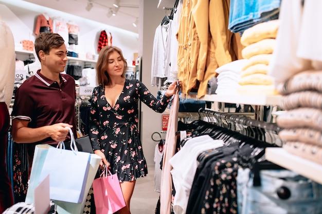 Una chica y un chico caminan entre perchas con ropa en una boutique, donde una chica elige las cosas por sí misma. un concepto de compras. una elección de ropa. viernes negro rebaja.