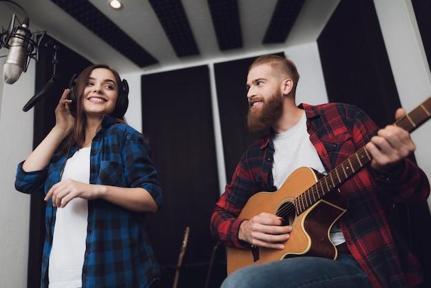 Chica y chico cantan canción a guitarra en un moderno estudio de grabación