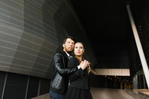 Chica y chico enamorado de la ropa oscura en el fondo de un edificio geométrico oscuro