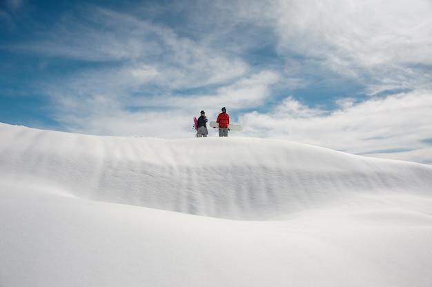 Chica y chico en equipo de esquí con tablas de snowboard en manos están parados en carretera cubierta de nieve