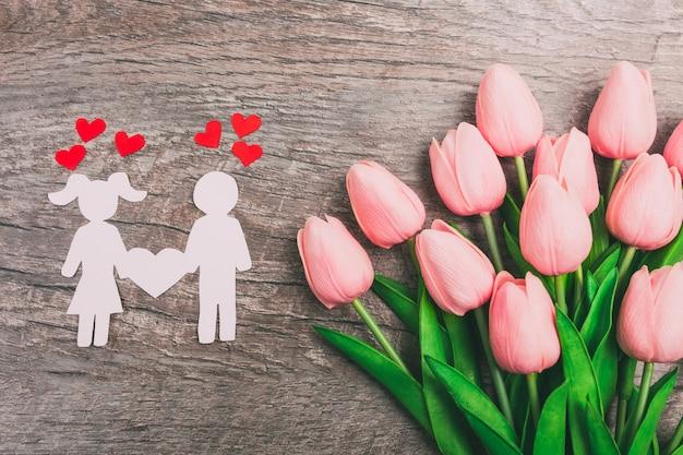 La chica y el chico están cortados de papel, sobre un fondo de madera, contra el fondo de un ramo de tulipanes rosados.