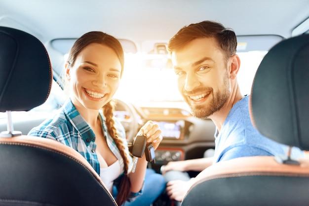 La chica y el chico están sentados en un auto nuevo y sonriendo.