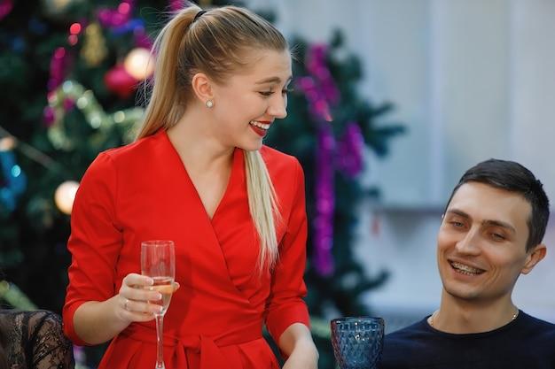 Chica y chico en la mesa navideña. la mujer hace un brindis con una copa de champán en la mano.