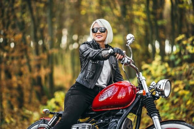 Chica ciclista bastante rubia en gafas de sol con motocicleta roja en la carretera en el bosque