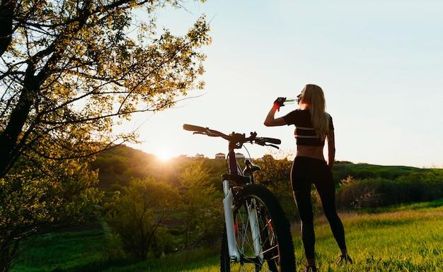 Chica ciclista bebe agua limpia después de entrenar cerca de su bicicleta bajo los rayos del sol naciente