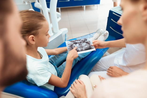 Chica en la clínica dental. dentista mostrar radiografía de la mandíbula.