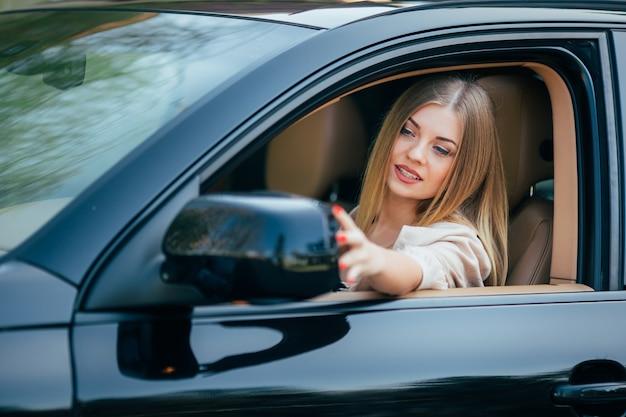 Chica en coche arreglar espejo de vista posterior