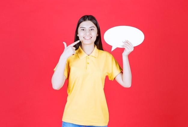 Chica en código de vestimenta amarillo sosteniendo un tablero de información ovale