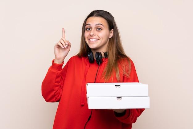 Chica cogiendo cajas de pizza sobre pared aislada
