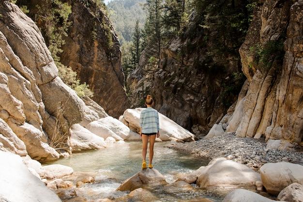 Chica con cola de caballo posando en rocas en el cañón