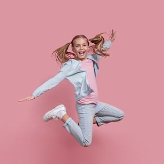 Chica con colas de caballo saltando y sonrisas