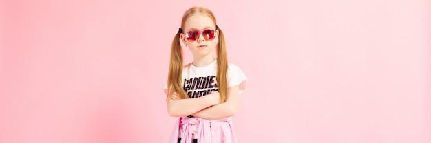 Chica con colas rojas un rosa. una chica encantadora con ropa deportiva brillante y lentes rosas cruzó los brazos sobre el pecho.
