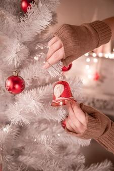 Chica colgando campana de juguete decorativo en la rama de un árbol de navidad.