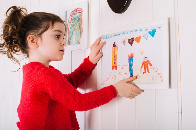 Chica colgando marco en la pared