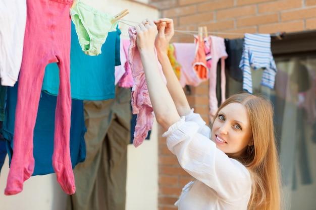 Chica colgando la ropa en la cuerda de tender la ropa