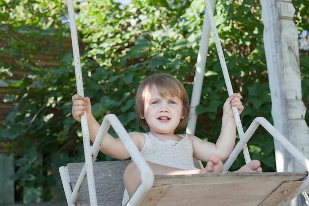 Chica en columpio en el parque de verano