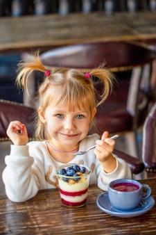 Chica come postre en la mesa. niño feliz come dulces. hermoso bebé sonriendo a la mesa. fiesta de té con un niño. graciosa come helado. el niño se está riendo en el almuerzo. hermosa chica come