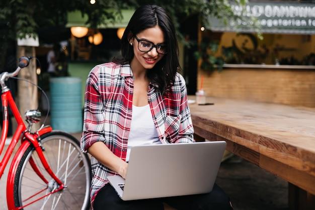 Chica complacida con cabello oscuro mirando la pantalla del portátil con una sonrisa mientras está sentado en la calle. foto exterior de mujer interesada escalofriante después de un paseo en bicicleta.