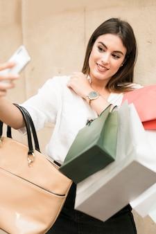 Chica de compras haciéndose un selfie