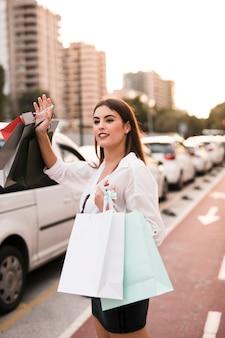 Chica de compras llamando un taxi
