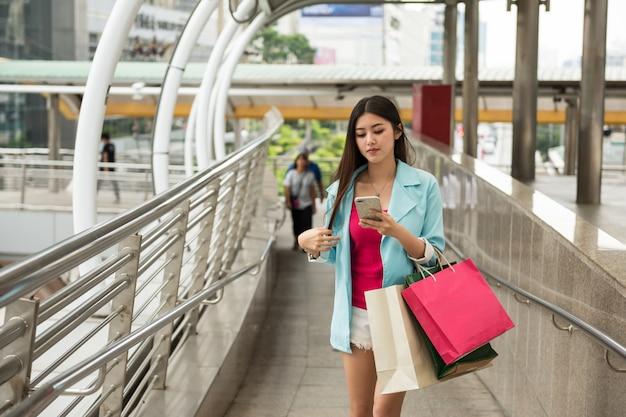 Chica de compras navegando ubicación de la tienda en la ciudad
