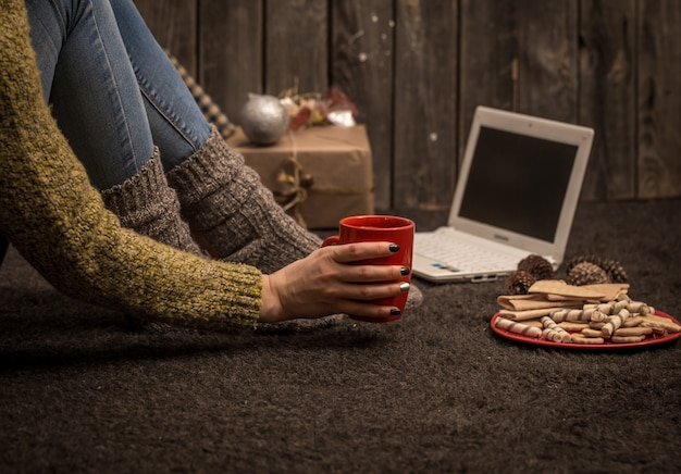 La chica con la computadora y con la hermosa decoración navideña y concepto de vacaciones