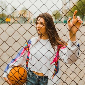 Chica con baloncesto detrás de valla