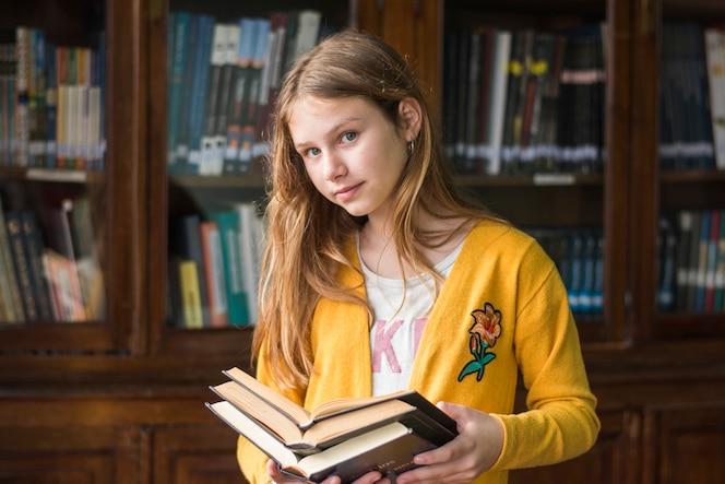 Chica con libros de pie junto a la estantería vieja