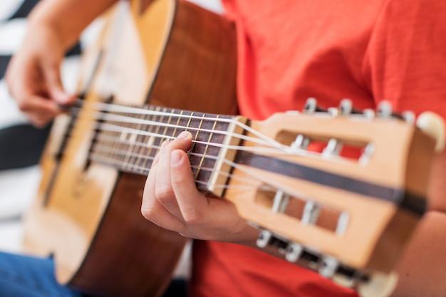 Chica concentrada practica con guitarra acústica sentarse en el sofá en casa