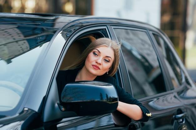 Chica conduce un coche y mira desde la ventana en el atasco de tráfico
