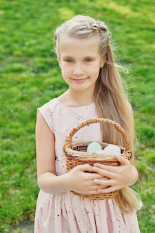Chica con conejo y huevos de pascua en el parque sobre hierba verde