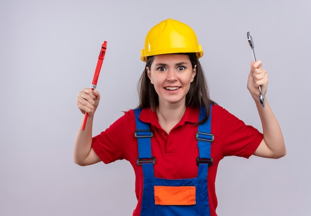 Chica constructora joven molesta sostiene llave de tubo y llave de taller sobre fondo blanco aislado con espacio de copia