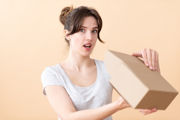 Chica consumidora sonriente con los ojos bien abiertos abre una caja de una tienda online.