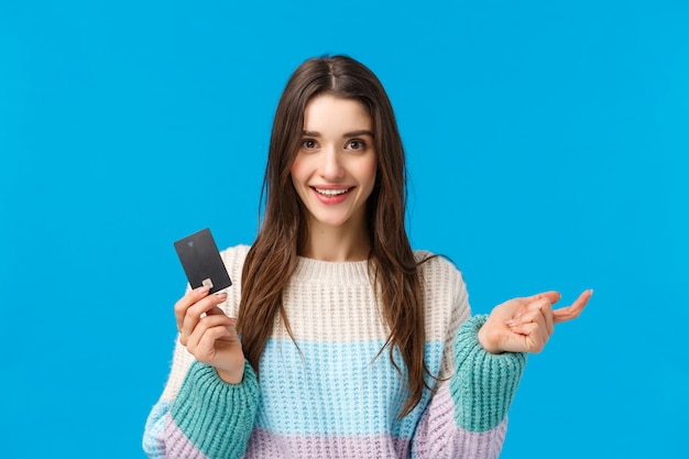 Chica contando pros del nuevo sistema bancario, doblando los dedos. atractiva mujer adicta a las compras lista para gastar todo el dinero en la tarjeta de crédito durante la temporada especial de descuentos de invierno, ir de compras, sonreír