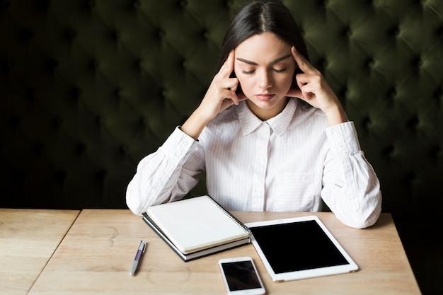 Chica contemplativa con gadgets y bloc de notas