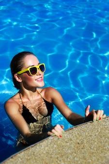 Chica contenta y bronceada posando en la piscina
