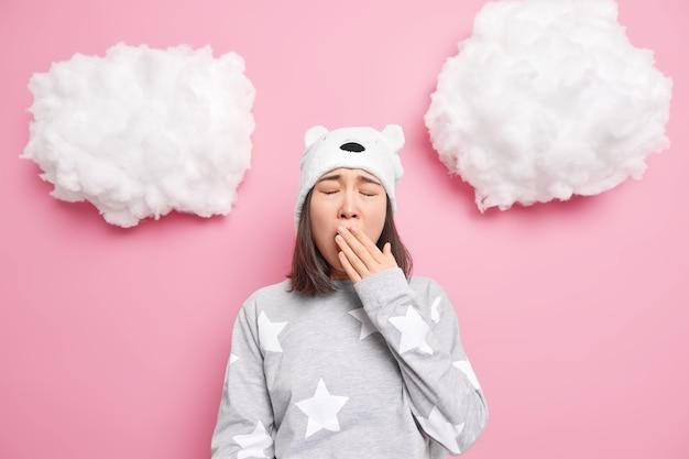 Chica contras boca bosteza quiere dormir tiene problema de insomnio vestida con ropa de dormir sombrero de oso suave aislado en rosa