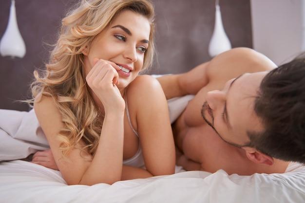 Chica coqueta en la cama con su novio