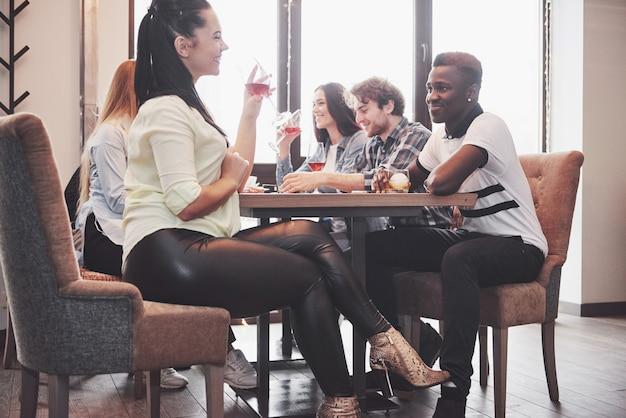Chica coqueteando con un chico tocando la pierna debajo de la mesa en un café mientras se divierte con los amigos. coquetea con tu pie durante el almuerzo