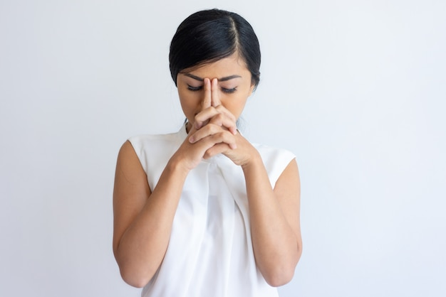Chica coreana cansada que sufre de dolor de cabeza