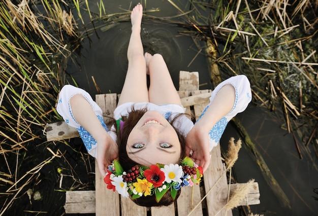 Chica en una corona de flores en su cabeza sentada en el puente y moja los pies en el río