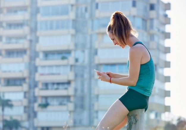 Chica corredor descansando y usando un teléfono inteligente construyendo un parque al aire libre