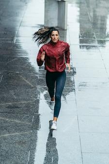 Chica corredor bajo la lluvia a lo largo de la ciudad